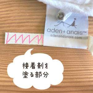 お食事エプロンの品質表示タグに通したテープに接着材を塗る