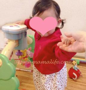 おもちゃでつかまり立ちをする生後8ヶ月女の子