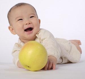 腹ばいでボールで遊ぶ赤ちゃん