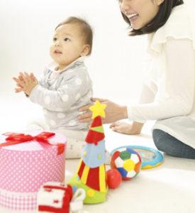 おもちゃと手をたたいて遊ぶ赤ちゃん