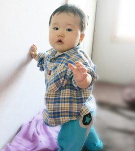 生後10ヶ月つかまり立ちをしている男の子の赤ちゃん